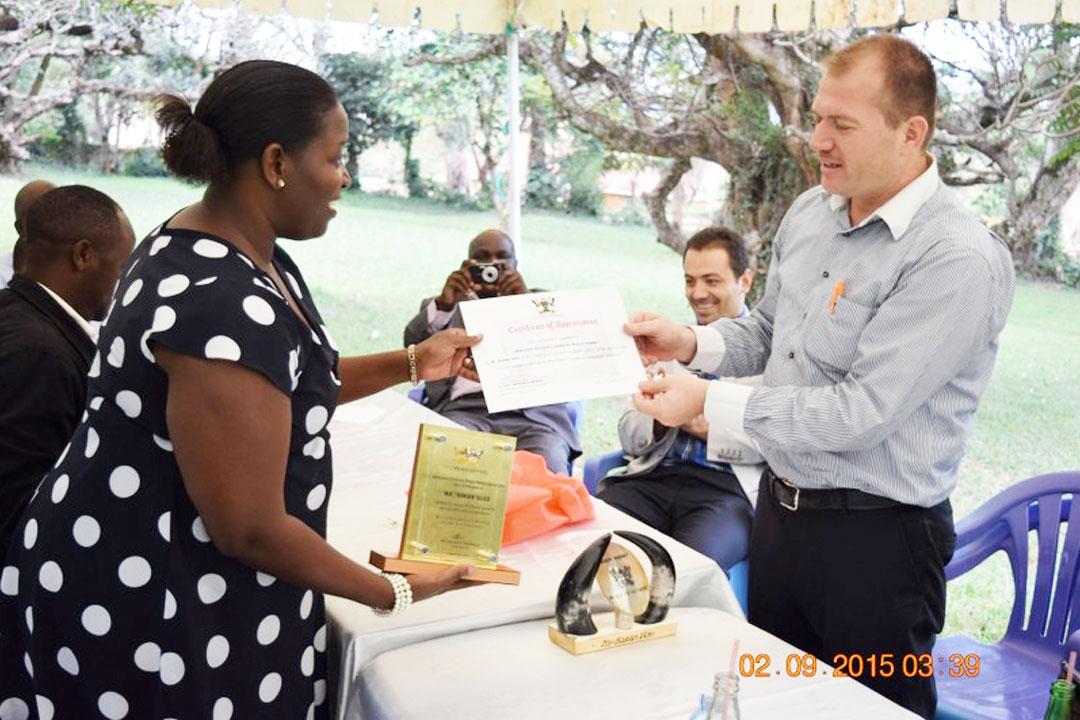 Dr. Helen Nambalirwa presents Mr. Hakani with a certificate and plaque. (Photo Credit: Davies RWABU)
